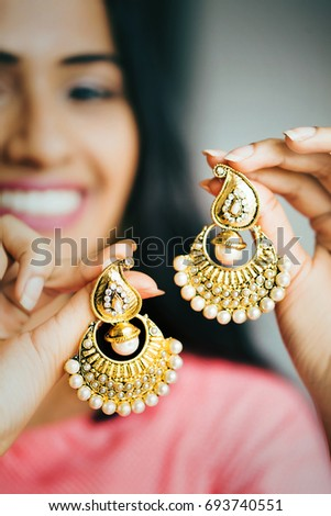 young beautiful Indian woman  holding a pair of gold and diamond earrings