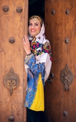 Young beautiful Iranian lady in traditional clothing looking out of a door in a traditional village of Abyaneh in Iran