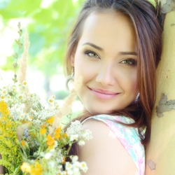 young beautiful lady with field flowers outdoor portrait, charming girl resting in summer park, toned and noise added