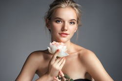 Young beautiful lady with rose on grey background. Skin care concept