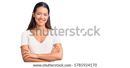Young beautiful latin girl wearing casual white t shirt happy face smiling with crossed arms looking at the camera. positive person.  Stok fotoğraf ©