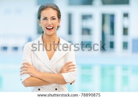 Young beautiful laughing business woman in glasses and with crossed hands against magnificent office.