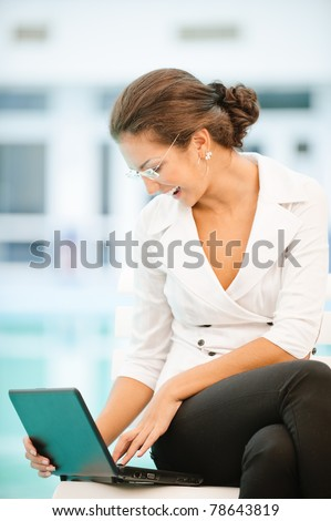 Young beautiful laughing business woman works on laptop.