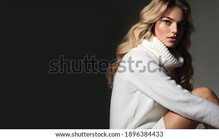 Young beautiful long-haired woman in a white knitted sweater in the studio on a black background. The woman is sitting and posing for the photographer.