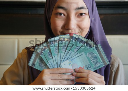 Young Beautiful Malaysian Muslim woman holding Ringgit notes