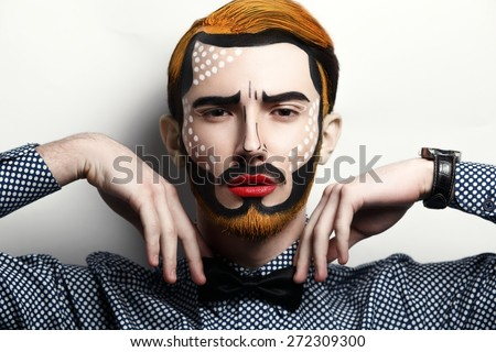 Young beautiful man. Bright creative make-up, style of comics. Red lips,black mustache, cheekbones .Yellow hair, beard. Stylish bow-tie, watch. Creative idea is good for a pin up poster, free place.