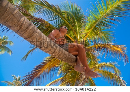 Young beautiful man sitting on the palm tree with coconut cocktail. Having summer fun during travel holidays vacation.