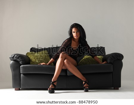 Young beautiful mixed race fashion model with long legs and stilettos wearing short sexy black skirt and lace top sitting cross legged on leather sofa with green cushions.
