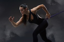 Young beautiful mixed race sportswoman on black background. Fit sporty woman doing run exercising