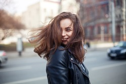 Young beautiful model girl smiles and looks back in the city. Dynamically young girl walks down the street.Hair fluttering in the wind.