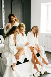 Young beautiful models sit on the bed in white coats and look at the ring
