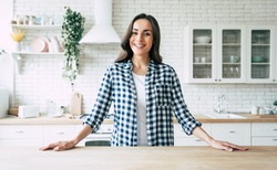 Young beautiful modern woman stands near table on kitchen at home.