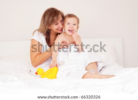 young beautiful mother and her baby on the bed at home after the shower
