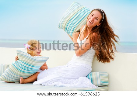 Young beautiful mother and her little cute daughter have a fun in beach cafe