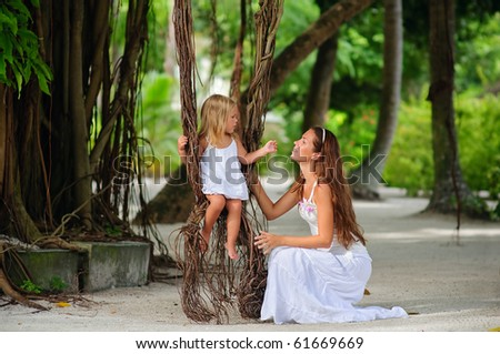 Young beautiful mother and her little cute daughter swinging on liana