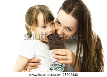 young beautiful mother and her little daughter eating chocolate