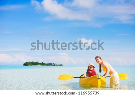 Young beautiful mother and her son preparing for kayaking - stock photo