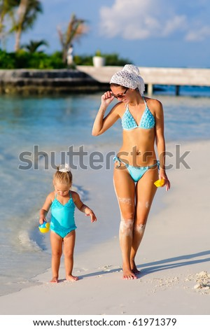 Young beautiful mother and her toddler pretty daughter in bikini walking on exotic beach
