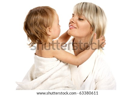 Young beautiful mother and small daughter after bathing sitting in towels. - stock photo