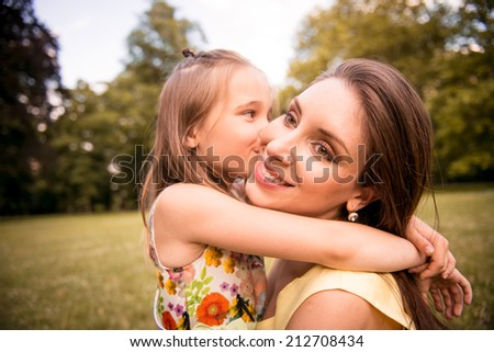 Young beautiful mother embraces her child (daughter) - outdoor in nature #212708434
