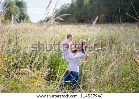 Young beautiful mother holding a baby girl in a meadow on a sunny day