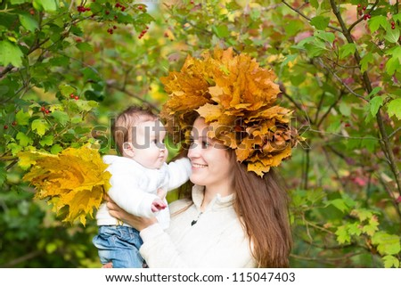 Young beautiful mother in a maple leaf wreath holding a sweet baby girl playing with yellow leaves
