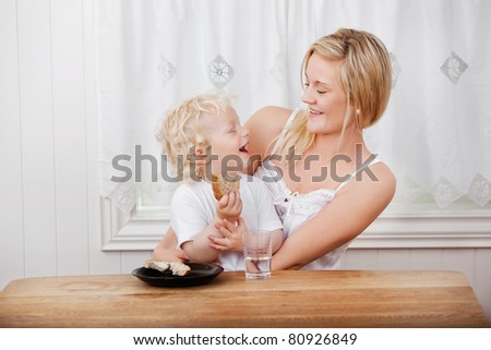 Young beautiful mother looking at cheerful baby boy eating bread at dining table