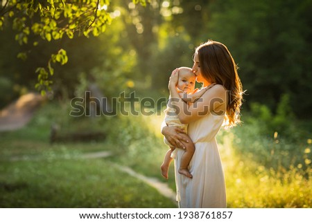 Young beautiful mother plays with her child outdoor.