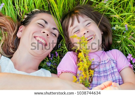 young, beautiful mother with little daughter, happy and laughing on a walk in the grass with flowers on a sunny, summer day. The concept of motherhood and a happy childhood