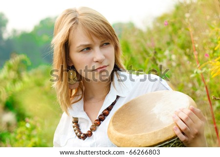 Young beautiful pensive girl with drum on a field