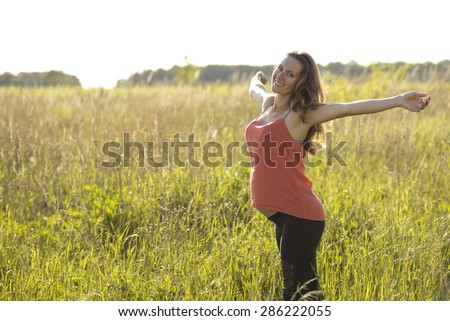 Young beautiful pregnant woman happy with open arms, in red a light summer dress, happy on the summer meadow in the grass in the bright sunny day. In anticipation of her child.