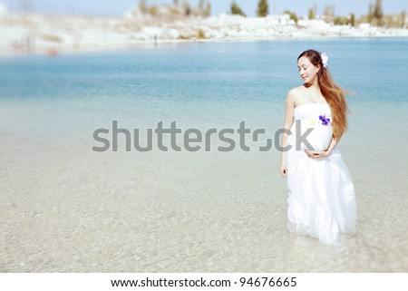 young beautiful pregnant woman in a white dress standing in the water against the background of beautiful scenery