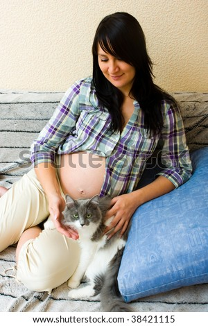 Young beautiful pregnant woman playing with her cat