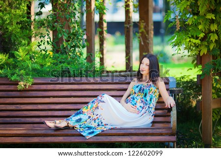 Young beautiful pregnant woman relaxing in the park