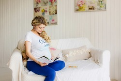 Young beautiful pregnant woman sitting on white sofa with a book with copy space. Blue and  white colors.