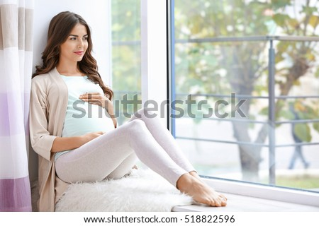 Young beautiful pregnant woman sitting on windowsill at home #518822596