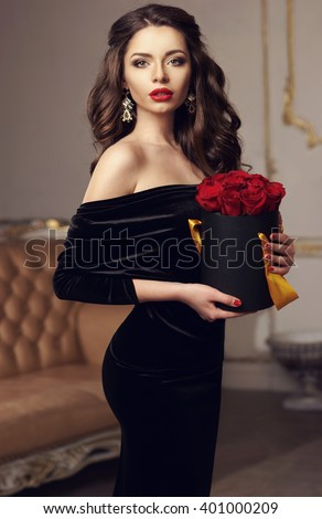 Young beautiful pretty girl standing and holding black box with red roses. Vogue fashion style studio portrait of sexy girl in black elegant dress standing in luxury interior
