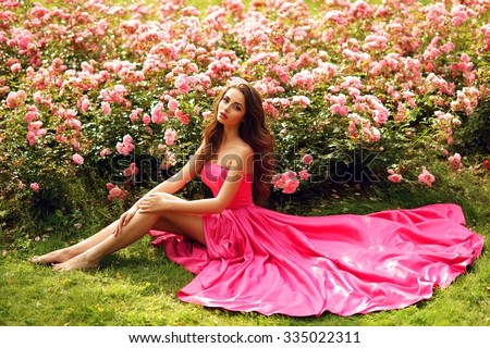 young beautiful pretty girl with curly hair in pink silk dress sitting on grass near bushes of. Black Bedroom Furniture Sets. Home Design Ideas