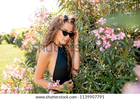 Young beautiful pretty woman with gorgeous long hair posing in swimming suite against bushes with pink flowers on a sunny summer day. Vogue style fashion sensual portrait. #1139907791