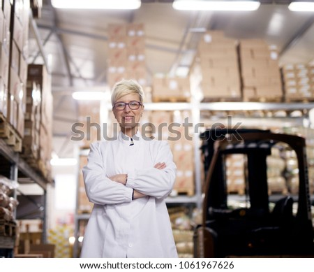 Young beautiful proud female worker is holding her arms crossed and smiling for the camera beside the forklift truck in a factory storage room.