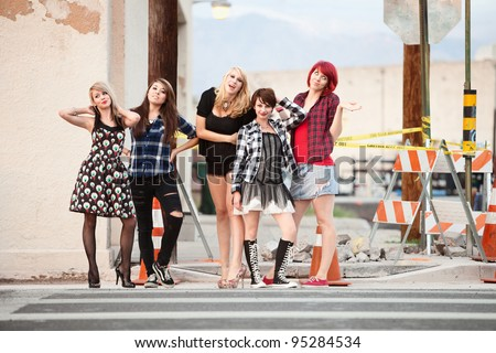 Young, beautiful, punky teen girls strike poses for the camera.