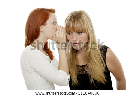young beautiful red and blond haired girls whispering in front of white background