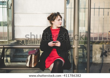 young beautiful red dressed vintage hipster woman sitting at the bus stop waiting, holding smart phone overlooking - commuter, technology concept