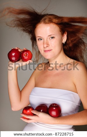 young beautiful red hair girl holds apples