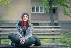 Young beautiful red hair girl sitting alone outdoors on the wooden bench on the street with hat and shirt feeling anxious and depressed after she became a homeless person