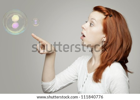 young beautiful red  haired girl look to soap bubbles and wondering in front of grey background