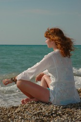 Young beautiful red-haired girl meditates, looking at the vastness of the sea