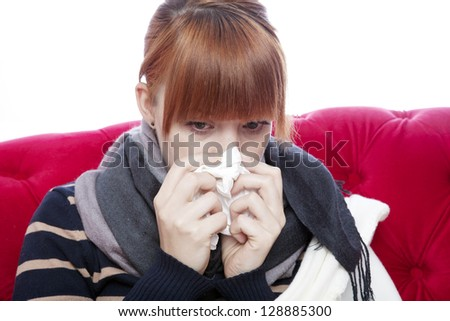 young beautiful red haired girl on red sofa with hanky on nose in front of white background
