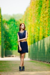 Young beautiful redhead girl in blue dress posing in Garden of Verssailles, France