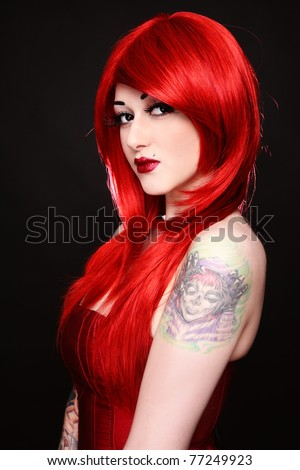 Young beautiful redhead girl with tattoo on her shoulder